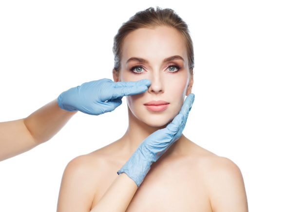 plastic surgery expert witness surgeon or beautician hands touching woman face